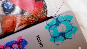 Kirjan perhoskuvitusta perhosaiheisen lakanan päällä