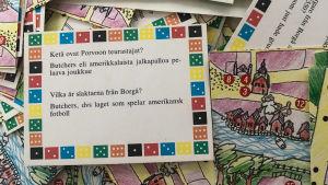 """Närbild på frågekort och spelplan som hör till Borgåspelet. På frågekortet står det: """"Vilka är slaktarna från Borgå? Butchers, dvs laget som spelar amerikansk fotboll""""."""