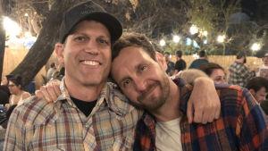 Michael Schwartz och Tyler Nilson står bredvid varandra och håller om varandra och ser rakt in i kameran och ler.