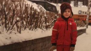 Kaari Mattila pikkutyttönä lumisessa katumaisemassa pulkan kanssa.