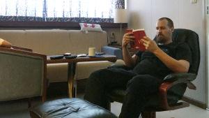 en skäggig man som läser en bok i en hytt.