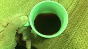 En kaffekopp i en grönfärgad omgivning.