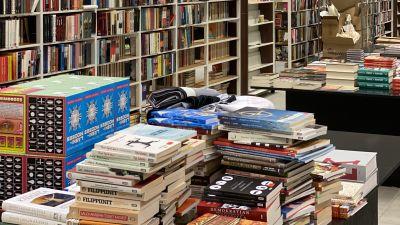 Böcker i travar framför bokhyllor.
