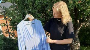 Elin Stråhlman blev student coronavåren 2020 och ser på sin ljusblåa festklänning ute i trädgården.