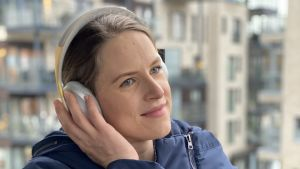 Närbild på Jonna Vuoskoski som står på en balkong och har hörlurar på sig.