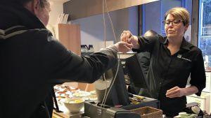 Anne Peltonen tar betalt av en lunchgäst.