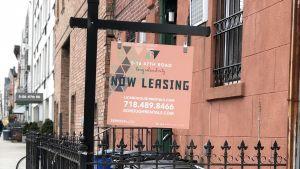 """Uthyres""-skylt vid sopstation vid lugn sidogata i New York."