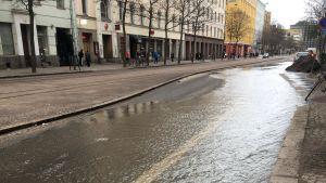 Vatten på Helsingegatan i Helsingfors efter att en huvudvattenledning skadats