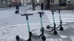 Fyra elsparkcyklar parkerade på trottoaren intill ett övergångsställe.