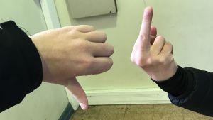 Två personer visar obscena gester med fingrarna