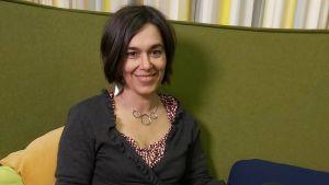 Annukka Såltin från utbildningsplanerare med kunskap om spelandet, sitter på en soffa med en bok i handen.