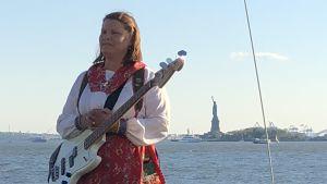 Kvinnlig gitarrist i folkdräkt, i bakgrunden Frihetsstatyn
