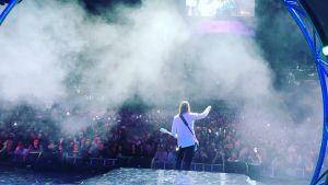 Person i svarta byxor och vit kavaj står med elgitarr på rökig scen, fotad bakifrån. I bakgrunden syns ett publikhav.
