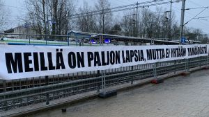 """Det hänger en banderoll på ett stängsel vid järnvägen. På banderollen står """"Meillä on paljon lapsia, mutta ei yhtään ylimääräistä""""."""