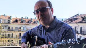 Petra Ingvesback man spelar gitarr på balkongen.