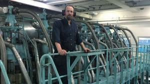 en skäggig man som står vid ett fartygs motor.