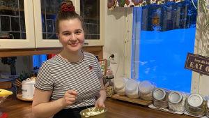 Jessica Jusslin står hemma i köket i förd sin servitörklädsel och uppsatt hår när hon vispar grädde i en bunke.