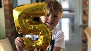 En pojke fyller fem år och ser glad ut.