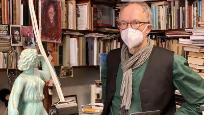 En äldre man i glasögon och med munskydd vid bokhyllor.
