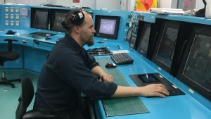 En skäggig man som sitter vid ett kontrollbord på en båt.
