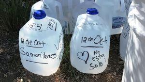 Vattenflaskor med text där det står Du är inte ensam på spanska.