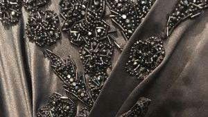 Ett svart tyg med dekorationer av svarta glaspärlor.