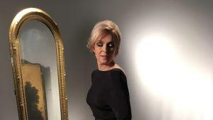 Anu Sinisalo som Marilyn Monroe i svart klänning framför en spegel.