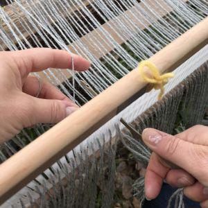 Varptrådarna flyttas en åt gången från den breda skåran, så att en blir kvar i den breda och en flyttas till den närmaste lilla hålet