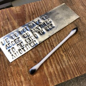 Alumiinilevy tekstillä ja pumpulipuikko puupalalla