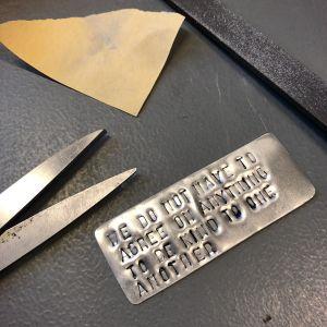 sakset, hiomapaperi, metalliviila ja alumiinipala tekstillä pöydällä