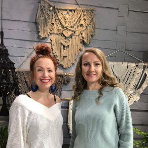 två kvinnor står framför många makraméarbeten