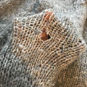 reikä neulepuserossa