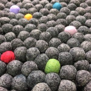 många tovade bollar i ull sydda tätt intill varandra