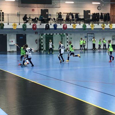 Unga pojkar spelar fotboll i en hall.
