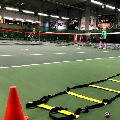 Barn som spelar tennis.