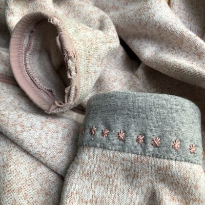 En tröja med en trasig mudd och en fin reparerad mudd