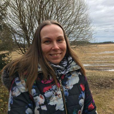 Kuvassa Johanna Paavola seisoo tilallaan. Taustalla näkyy viljapelto.