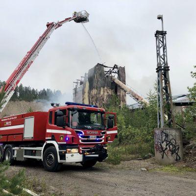 Palomies ruiskuttaa vettä nostokoriauton korista liekkeihin.