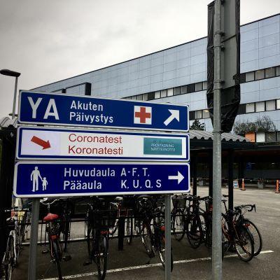 Cyklar i en cykelställning utanför ett sjukhus.