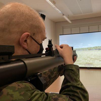 Person visar hur ett raketgevär fungerar när man tränar med en simulator inomhus.
