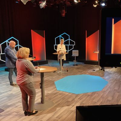 Ett foto taget bakom kullisserna i en tv-studio inför en diskussion. På bilden syns tre personer stå vid varsit bord, en fjärde person syns på en tv-skärm i hörnet.