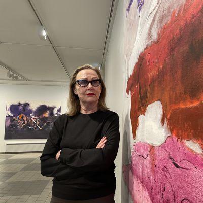 Taiteilija Marjatta Tapiola seisoo suuren taidemaalauksensa vieressä kädet puuskassa taideteosta tutkien.