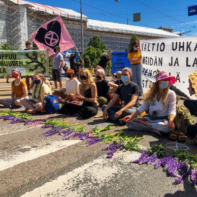 Personer demonstrerar med att sitta på bilvägen.