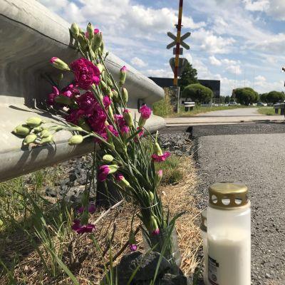 Kynttilä ja kukkia Porin Karjarannan tasoristeyksen vieressä