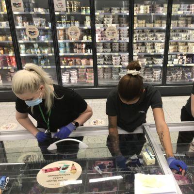 Myyjät katsovat kylmäaltaaseen kaupassa.