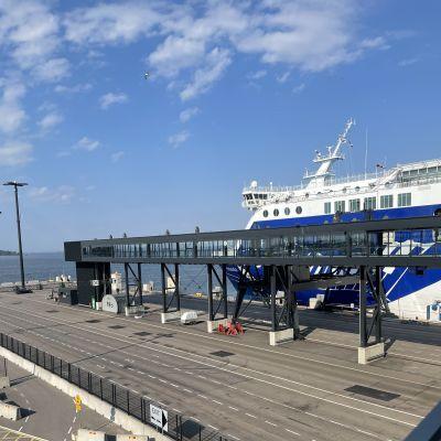 En bilfärja målad i vitt och blått ligger förtöjd vid en betongkaj. I förgrunden syns en gångbro från terminalen till färjan.