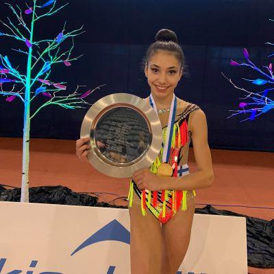 Nuori nainen voimisteluasussa esittelee palkintolautastaan.