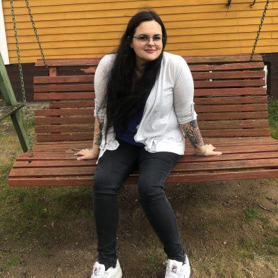 en ung kvinna i mörkt hår och med tatueringar på armarna. Hon sitter i en gunga.