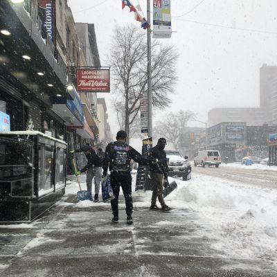 Folk skyfflar bort snö på en gata i New York.