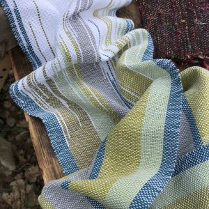 vävd halsduk som skiftar i färg i varpningen